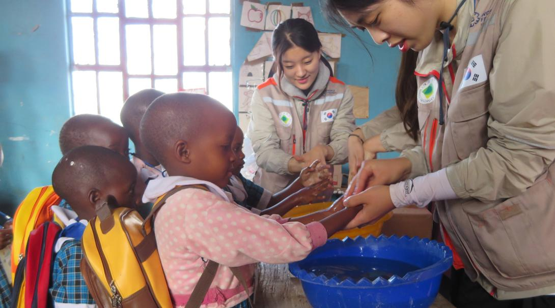 A couple of Korean teaching volunteers show young children how to wash their hands in Ghana while doing their internship with Projects Abroad.